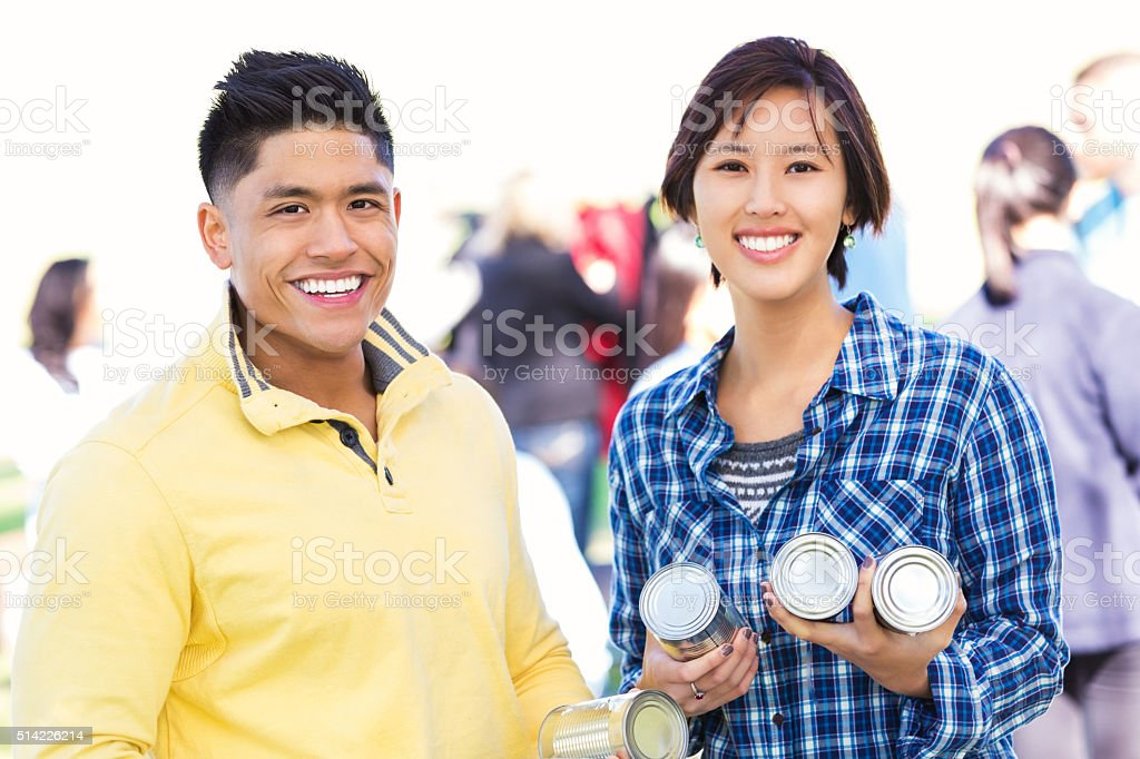 Asian couple donating items at food drive stock photo