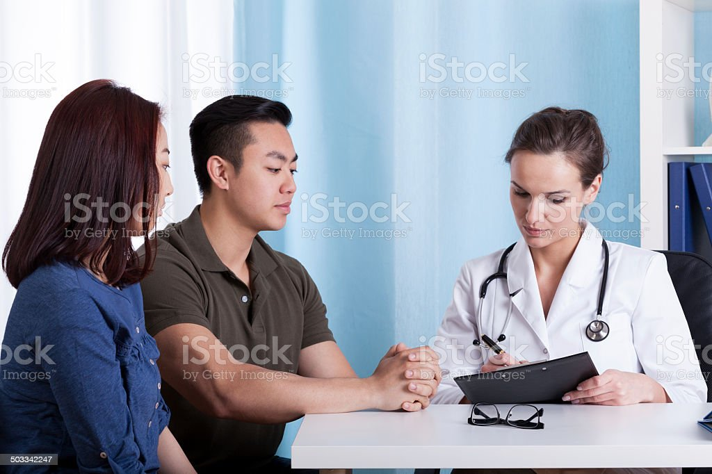 Asian couple during visit at doctor's office stock photo