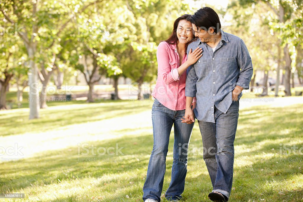 Asian couple holding hands walking in park royalty-free stock photo