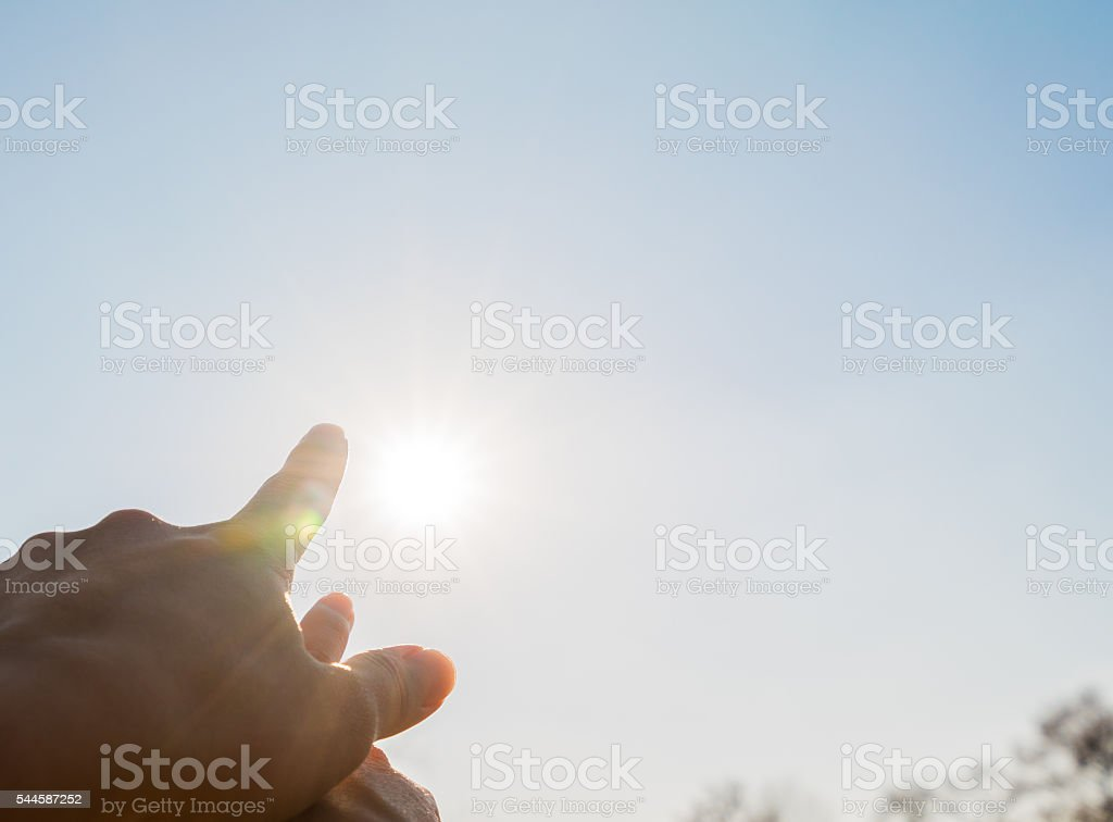 Asian couple pointing at sun together stock photo