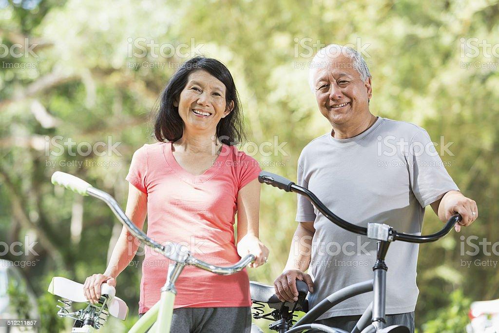 Asian couple riding bicycles stock photo