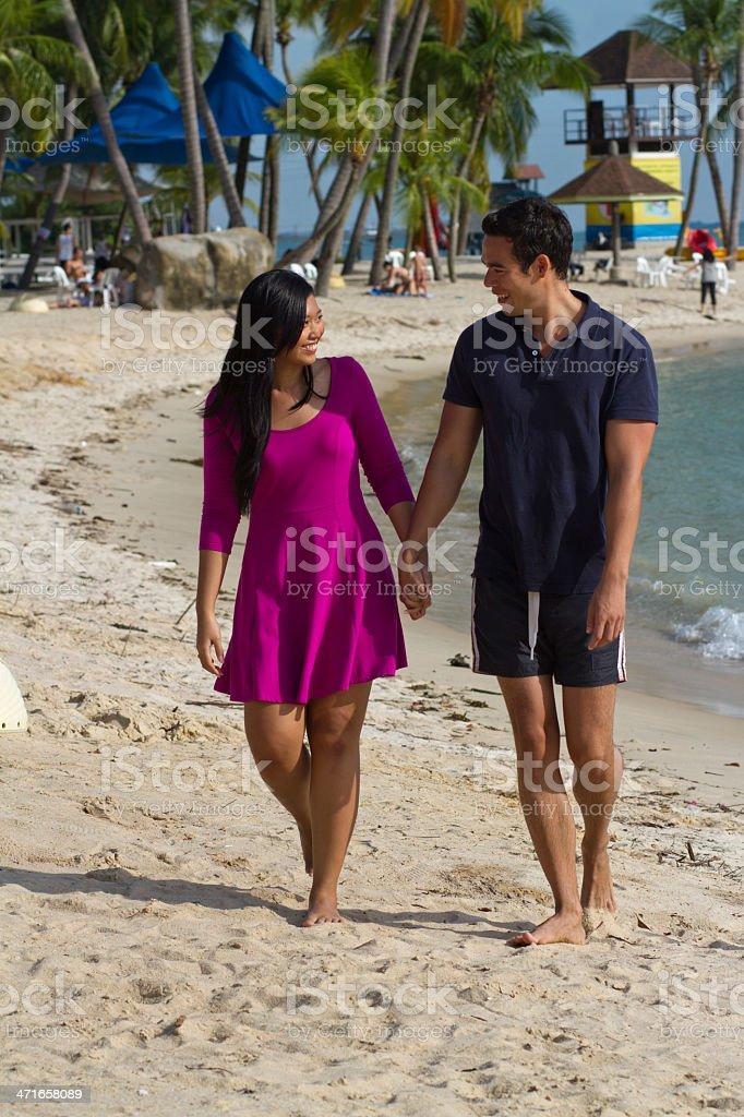 Asian couple strolling along beach royalty-free stock photo
