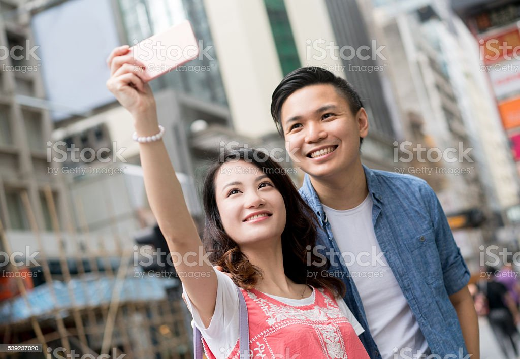Asian couple taking a selfie on the street stock photo