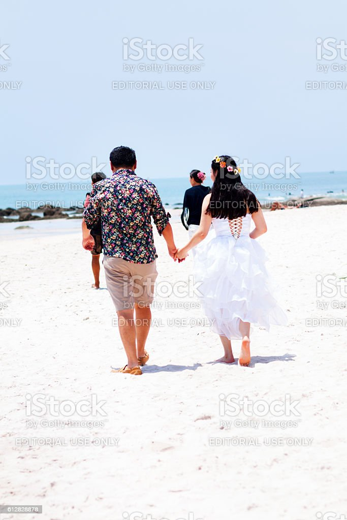 Asian couple walking and holding hands on beach stock photo