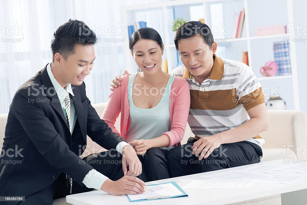 Asian couple with financial advisor sitting on sofa at table royalty-free stock photo