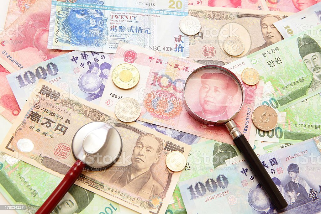 asian currency, with magnifying glass and stethoscope stock photo