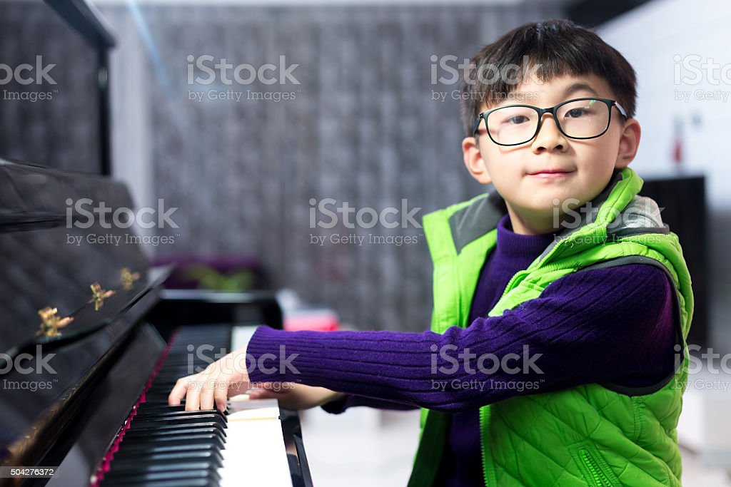 Asian cute boy playing piano at home stock photo