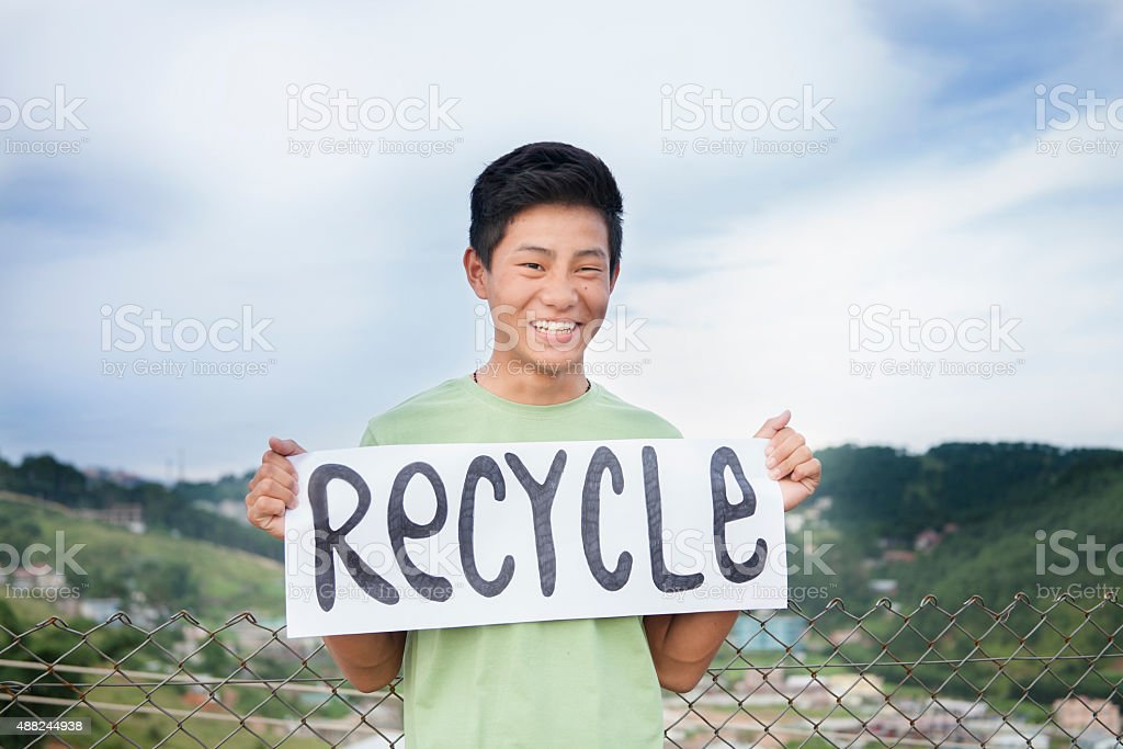 Asian descent teenage boy holds 'recycle' sign outdoors. stock photo