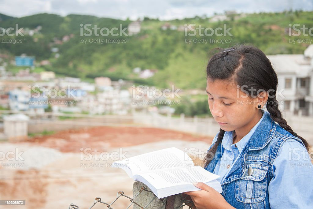 Asian descent, teenage girl reading a book outdoors. City. stock photo