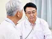 asian doctor checking a senior patient
