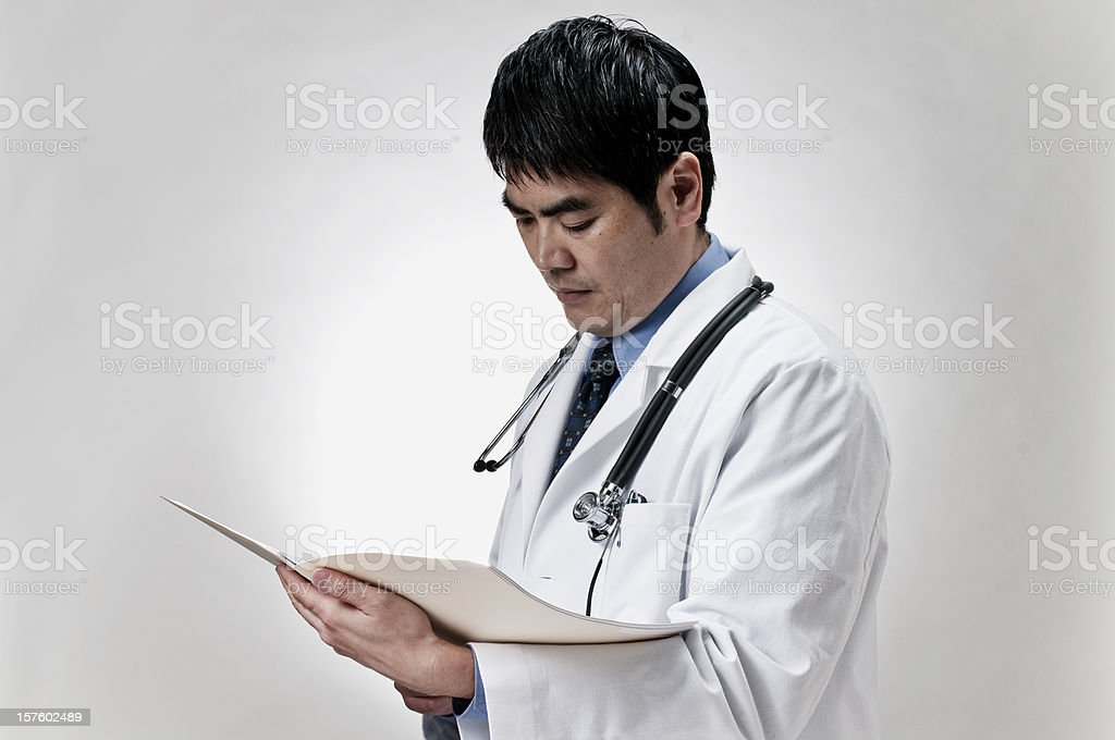 Asian doctor reading reports royalty-free stock photo