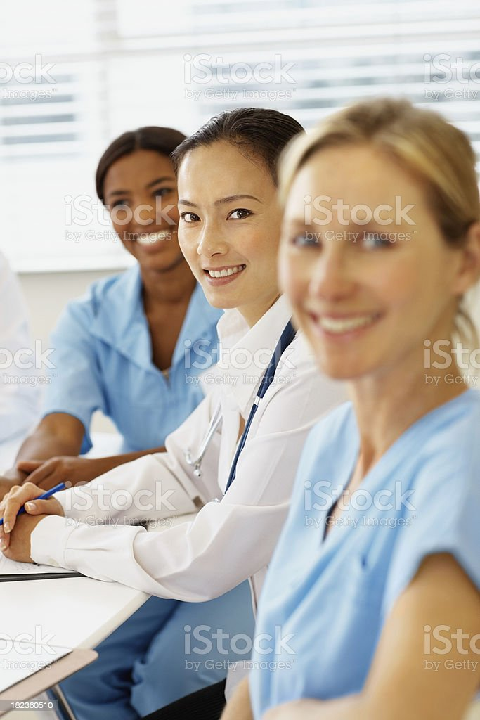 Asian doctor sitting with other female colleagues royalty-free stock photo