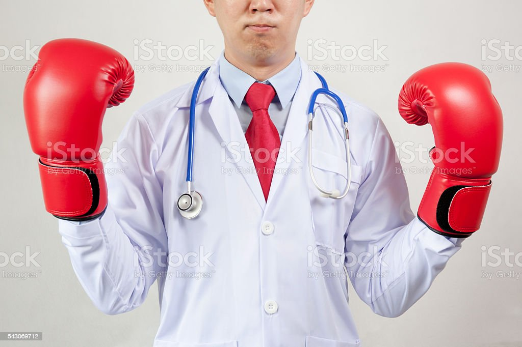 Asian Doctor wearing boxing gloves in white background stock photo