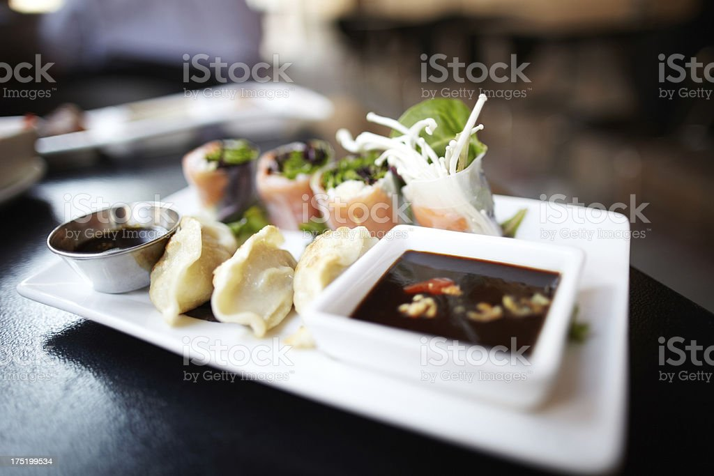 Asian dumplings gyozas and spring rolls on plate stock photo