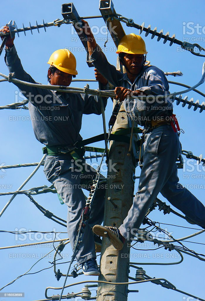 Asian electrician climb high, work on electric pole stock photo