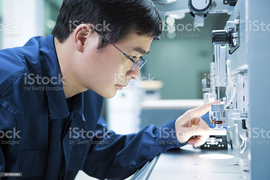 Asian Electronics engineer tinkering with equipment stock photo