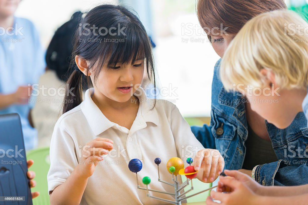 Asian elemenaty school student studying solar system in science class stock photo