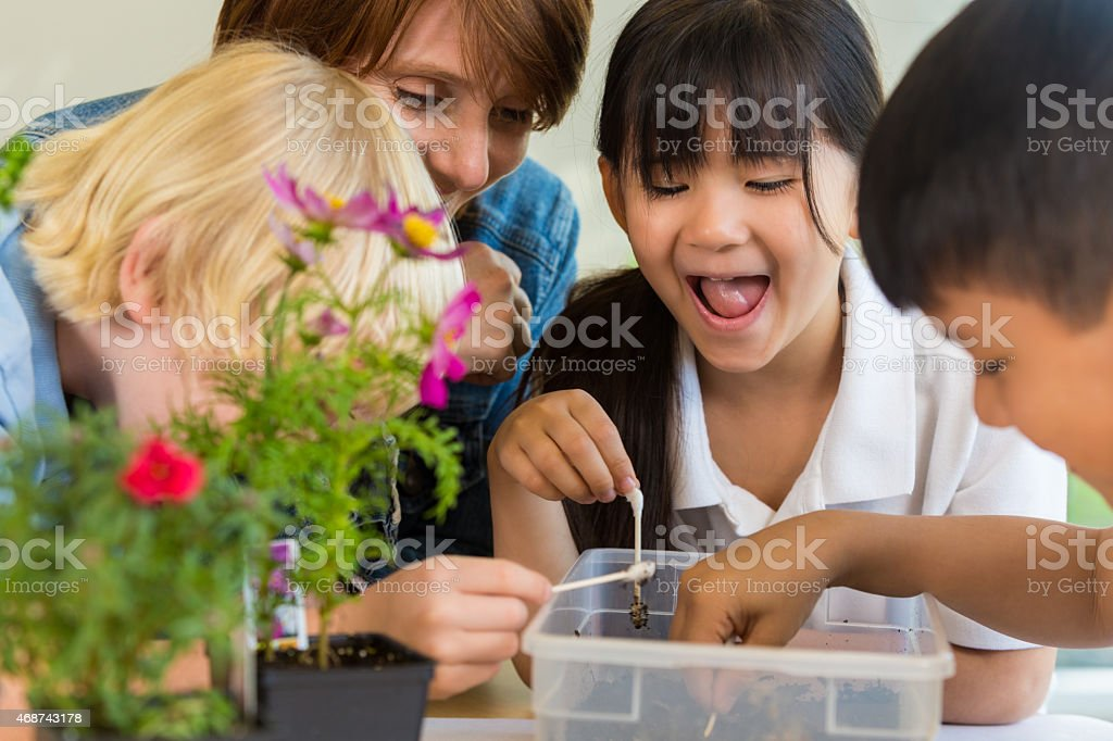 Asian elementary student smiling while doing science experiment with classmates stock photo