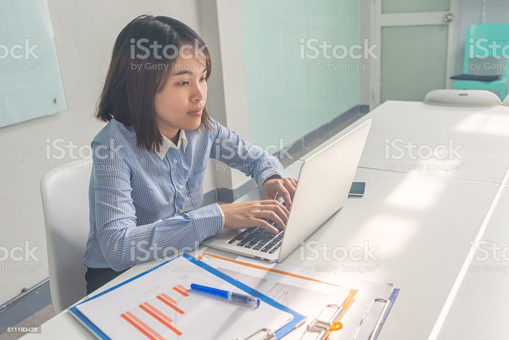 Asian employee using laptop to answer customers' questions on Internet stock photo