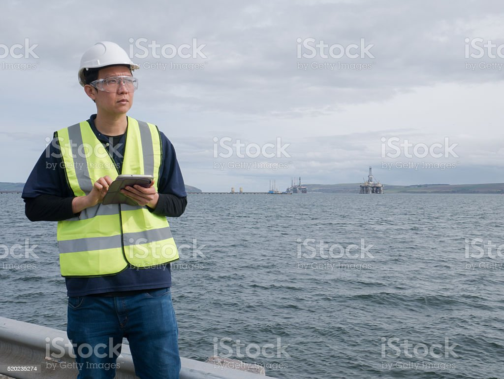 Asian engineer holding a tablet and standing stock photo