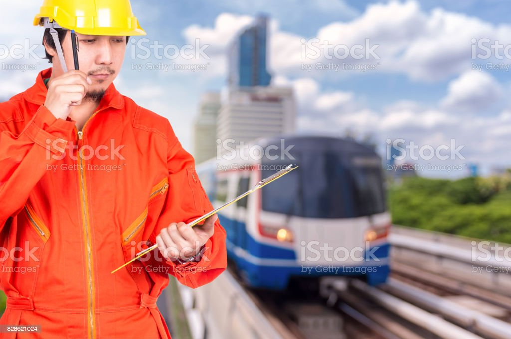 Asian engineers thinking and holding the note pad on abstract Blurred photo of sky train, transportation industrial concept stock photo