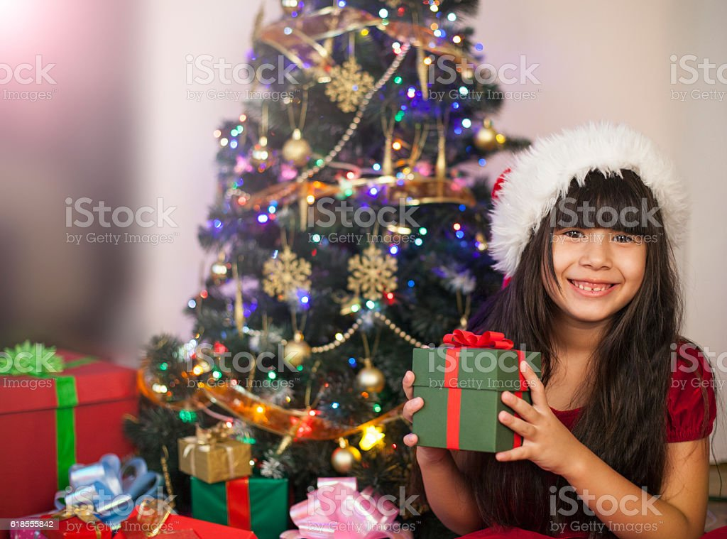 Asian excited little girl holding gift box on Christmas day stock photo