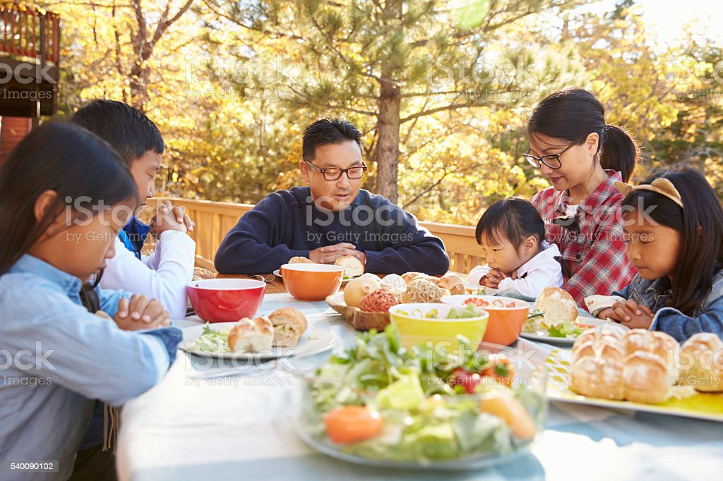 Asian family at a table on a deck say a prayer before stock photo