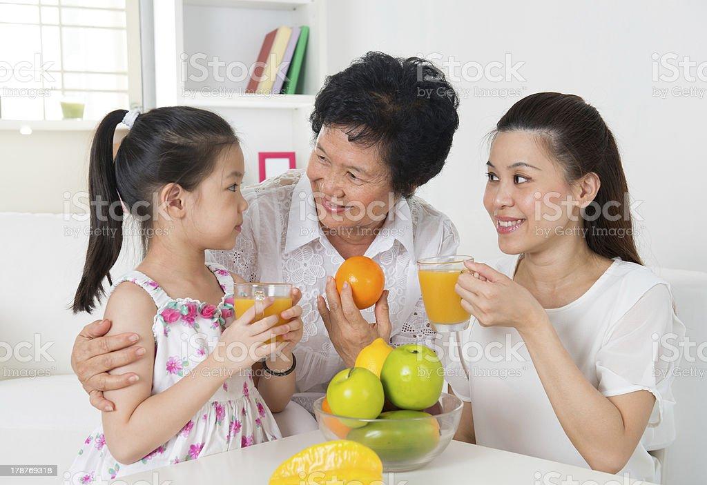 Asian family drinking orange juice. royalty-free stock photo