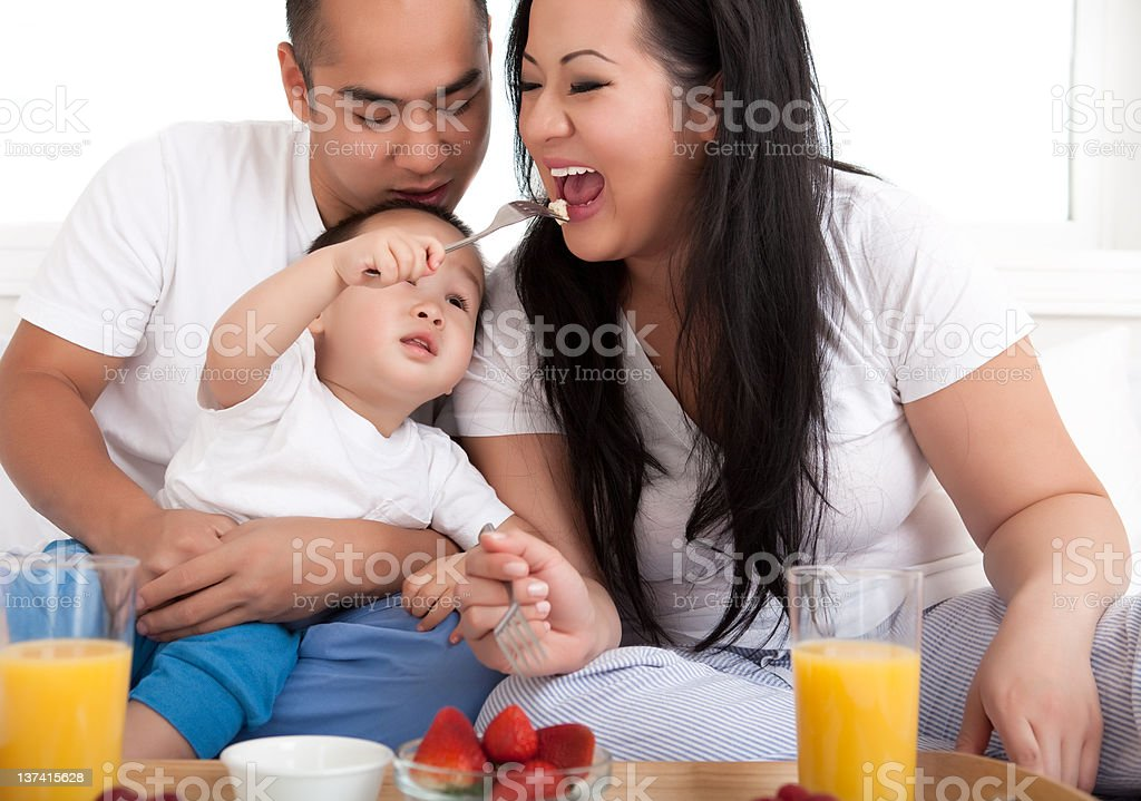 Asian family eating breakfast in bed royalty-free stock photo
