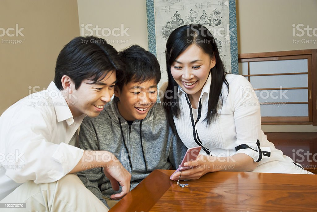 Asian family, looking at a mobile phone together stock photo