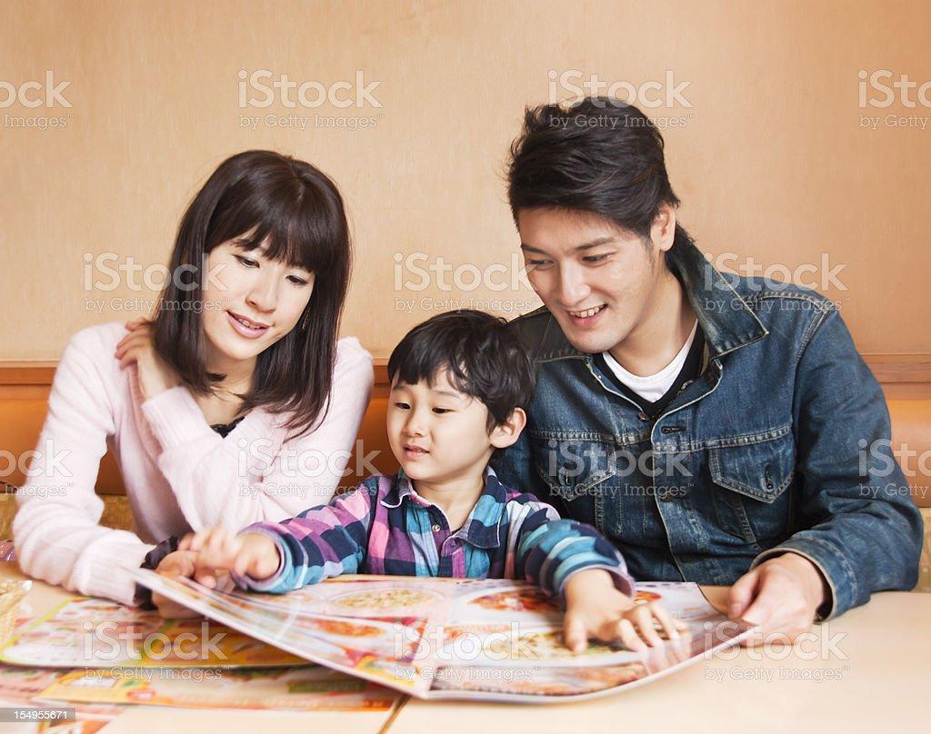 Asian family, looking at a restaurant menu stock photo