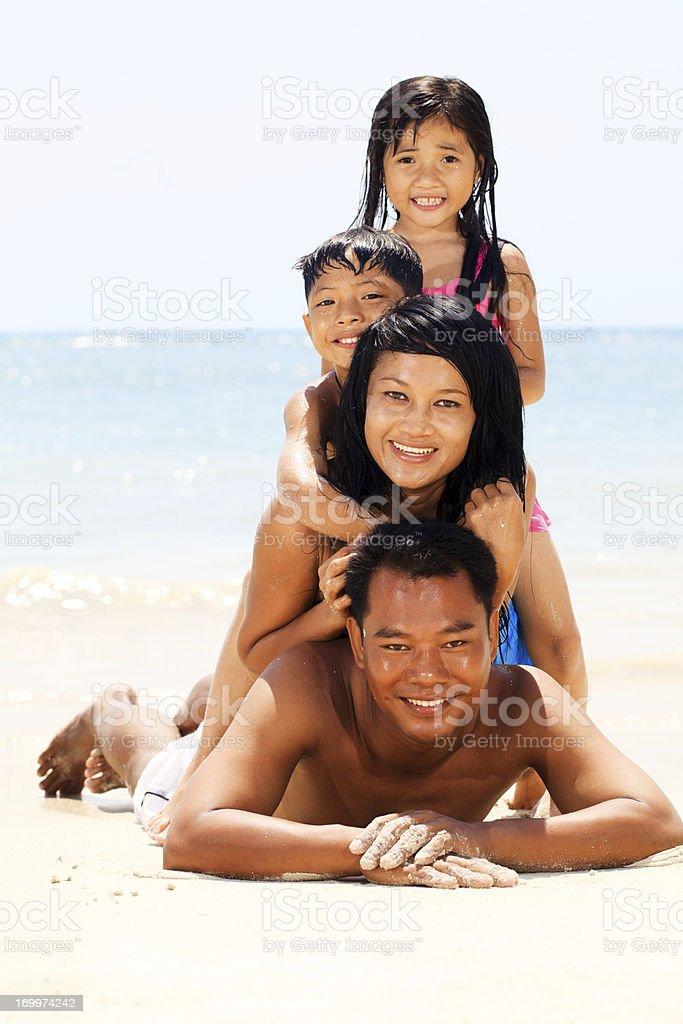 Asian family making a human pyramid on the beach. royalty-free stock photo