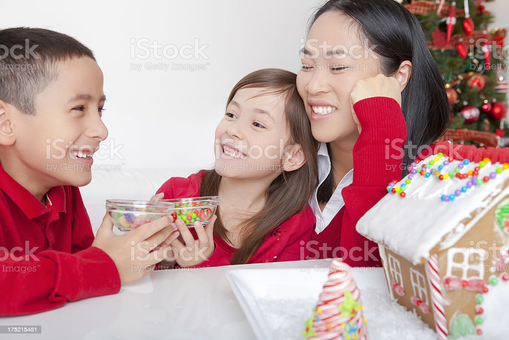 Asian family making gingerbread house royalty-free stock photo