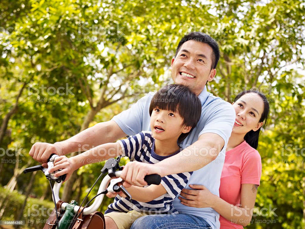 asian family riding bike in park stock photo