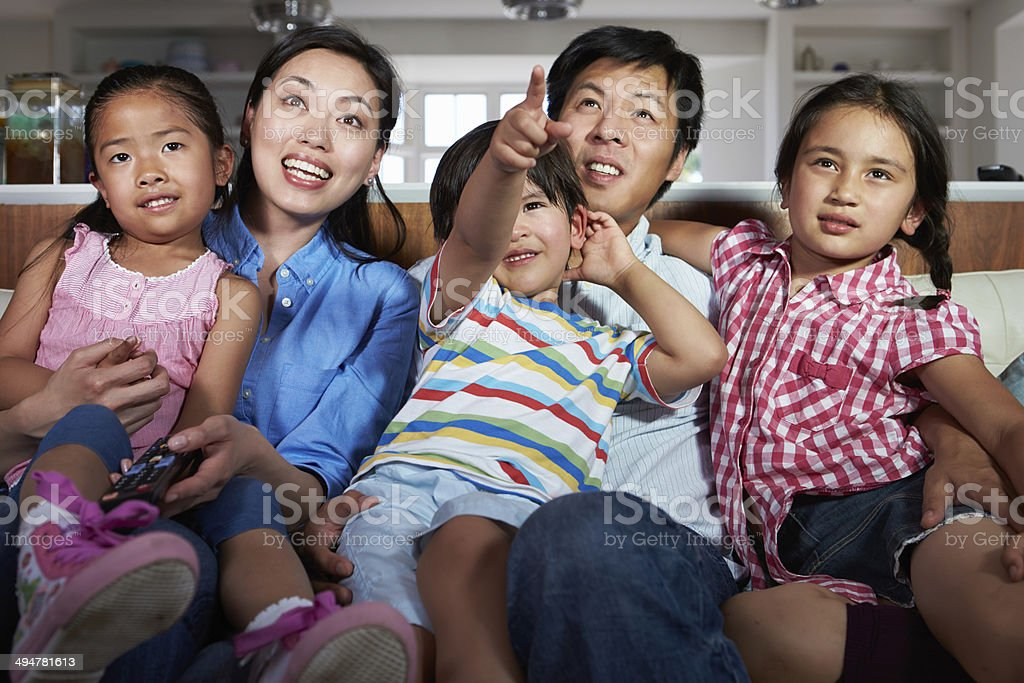 Asian Family Sitting On Sofa Watching TV Together stock photo
