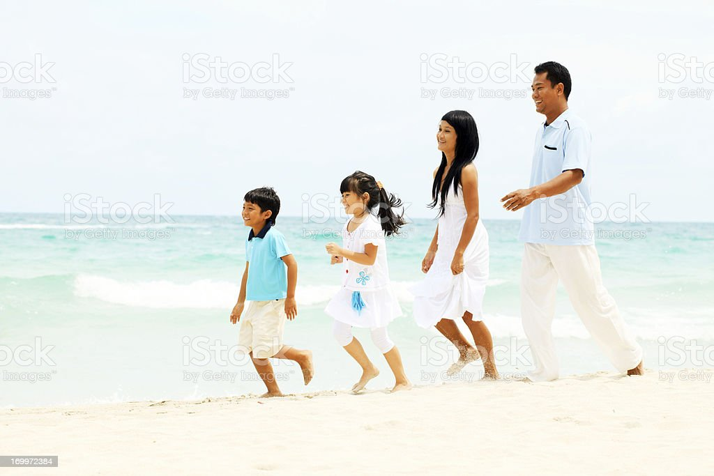 Asian family walking on the beach. royalty-free stock photo