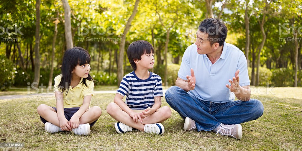 asian father and children talking in park stock photo