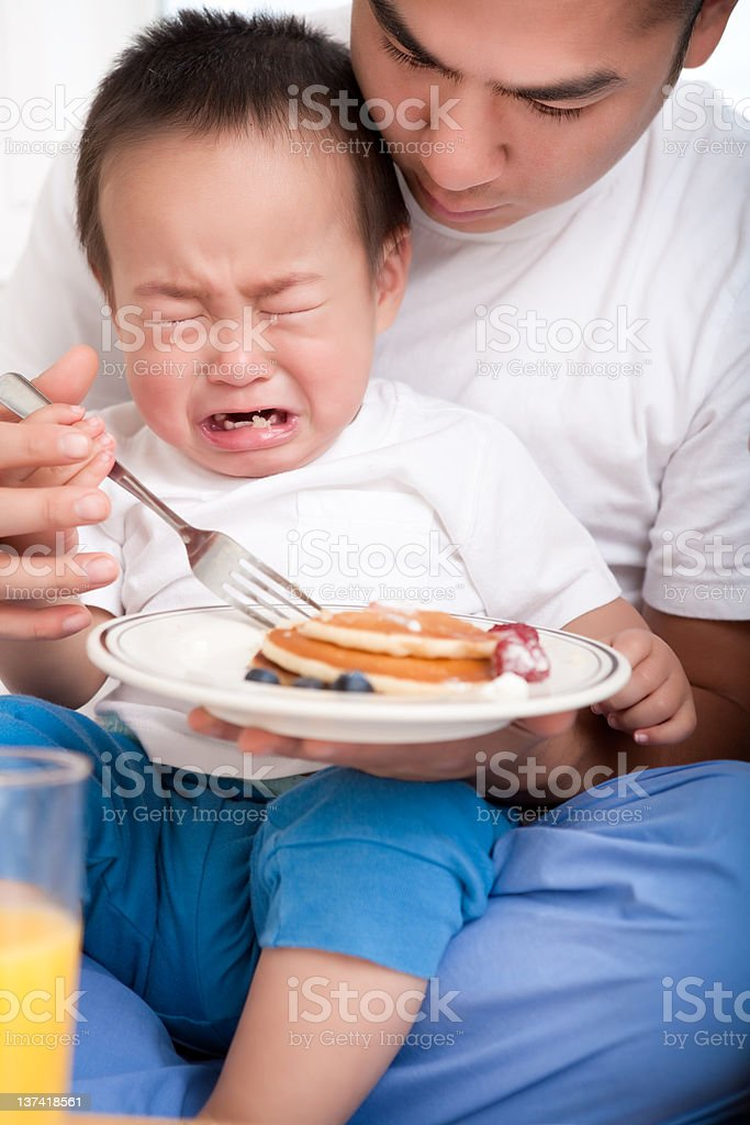 Asian father and son eating breakfast in bed royalty-free stock photo