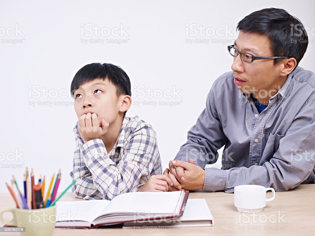 asian father and son having a serious conversation stock photo