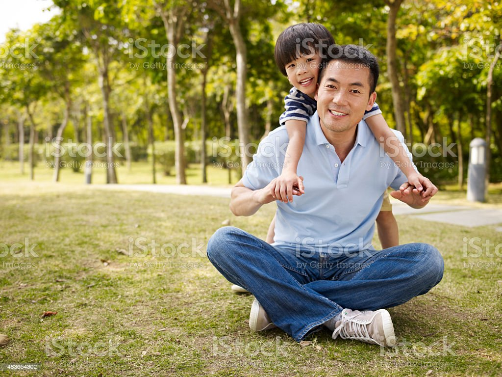 asian father and son having fun in park stock photo