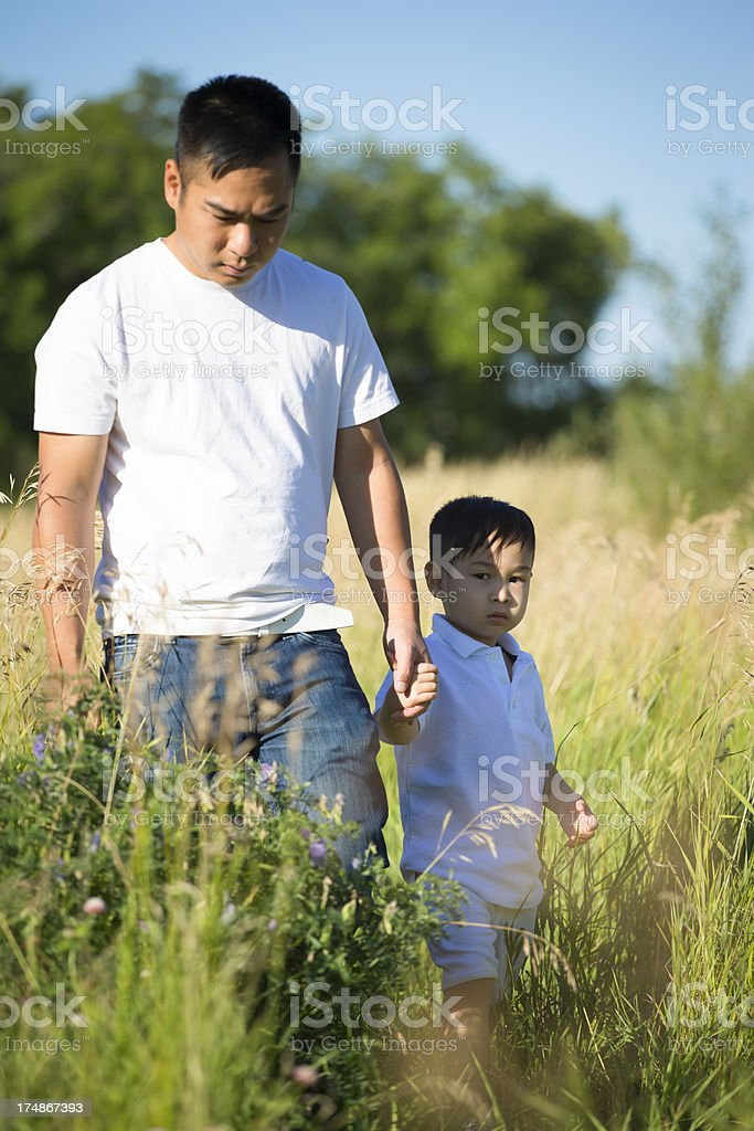Asian father and son in grass field royalty-free stock photo