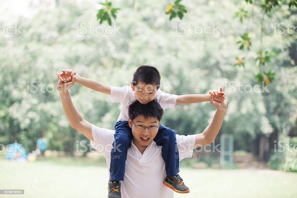 Asian father holding son hands happily oudoors stock photo