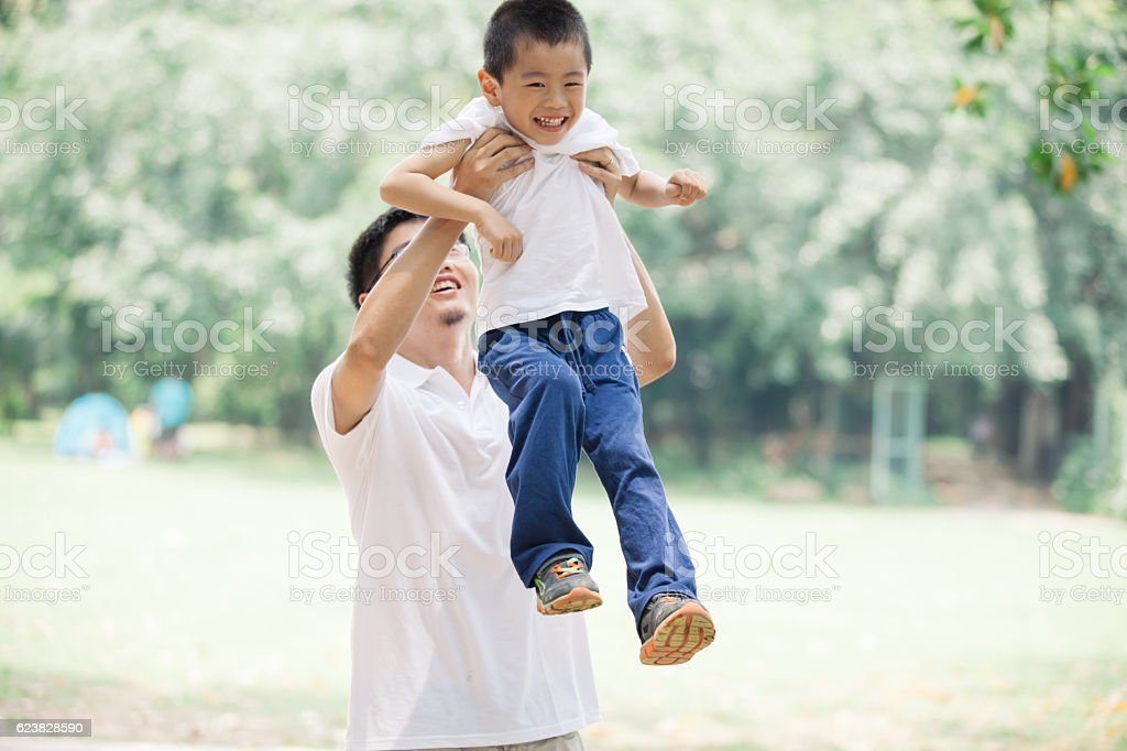 Asian father lifting son happily oudoors stock photo
