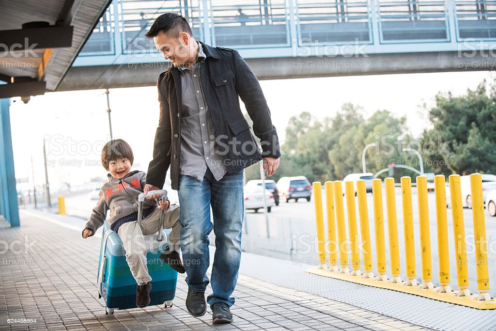 Asian Father Pulls Son on Suitcase Waiting for the Train stock photo