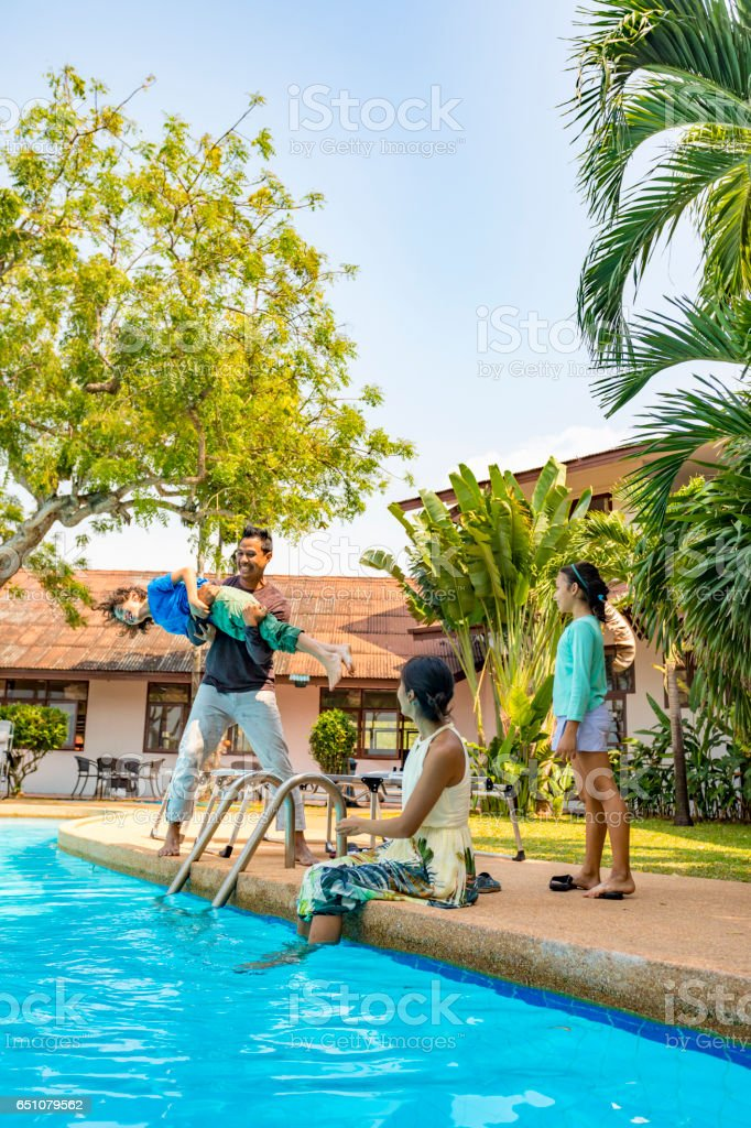 Asian Father Throwing His Son in the Pool on a Resort Vacation stock photo