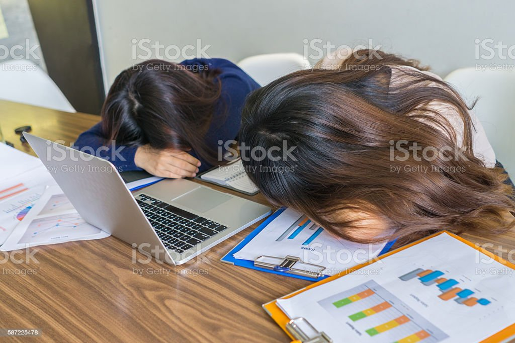 Asian female feel tired and sleepy after working overtime stock photo