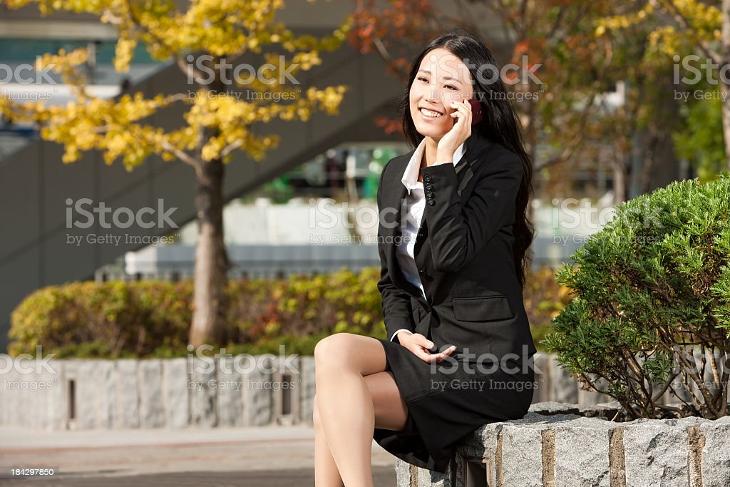 Asian Female in Suit Uses Cell Phone royalty-free stock photo