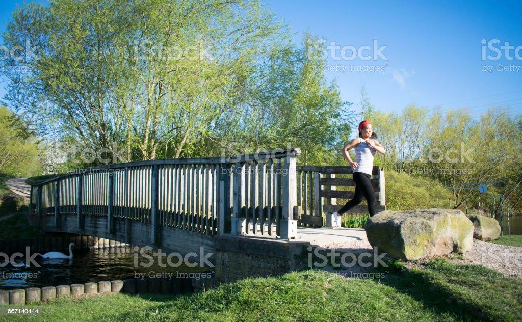 Asian Female Jogging Across Bridge stock photo