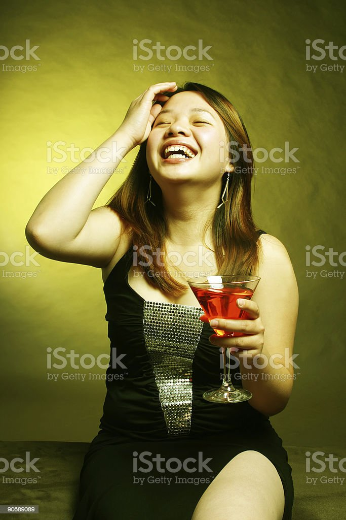 Asian female laughing while holding a cocktail 1800 x 2700 royalty-free stock photo