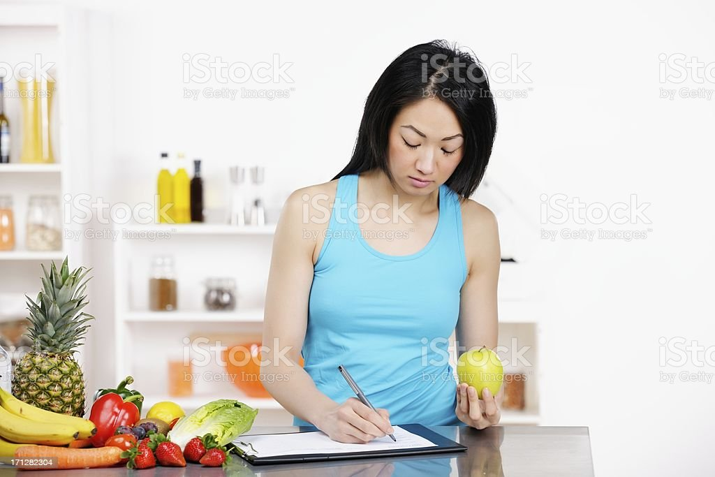 Asian Female Nutritionist Documenting Diet Plan royalty-free stock photo